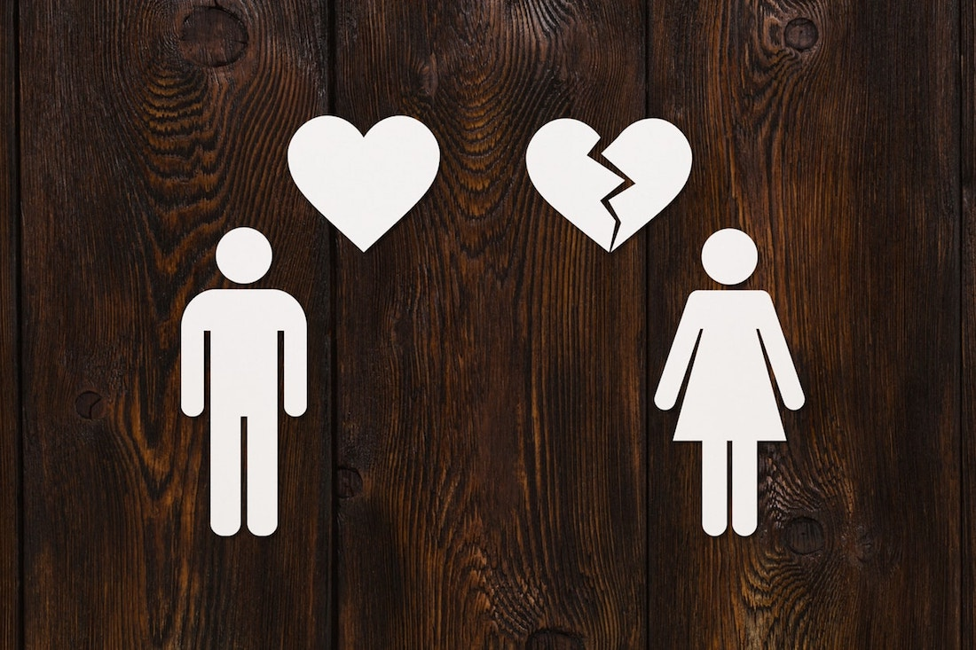 Paper man with heart and woman with broken one on wooden background