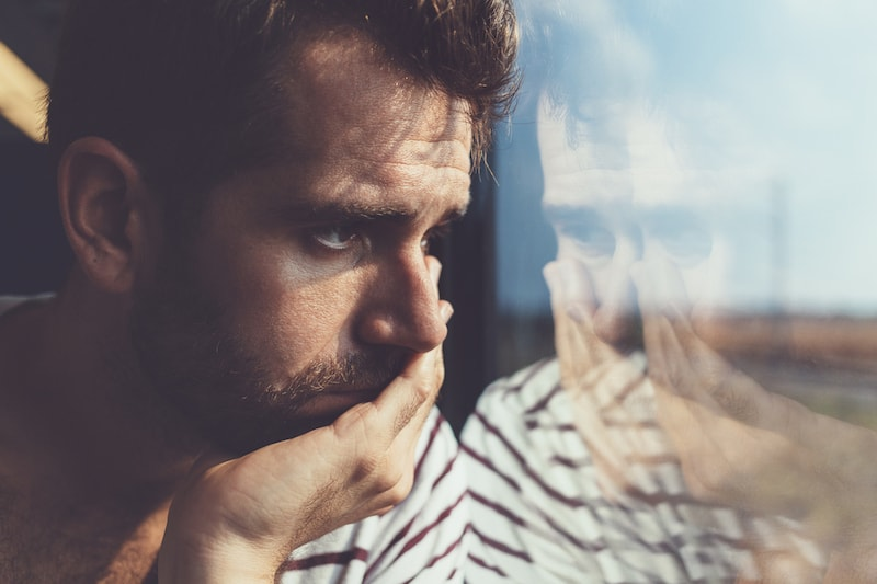 worried man looking out window